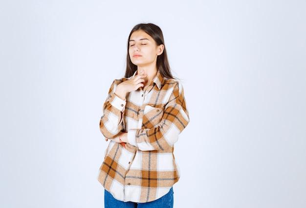 Ragazza in abiti casual in piedi e in posa sul muro bianco.