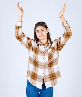 Ragazza in abiti casual in piedi e alzando le mani sul muro bianco.