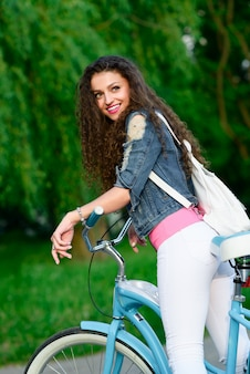 Young girl in casual clothes with a beautiful smile and curly hair rides a bicycle in the city in the summer