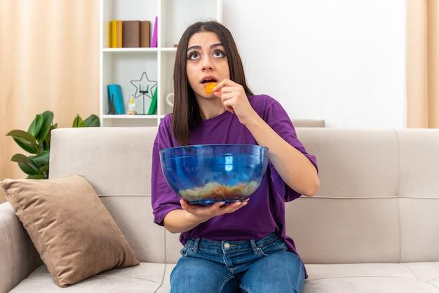 Giovane ragazza in abiti casual con una ciotola di patatine che mangia e sembra incuriosita seduta su un divano in un soggiorno luminoso