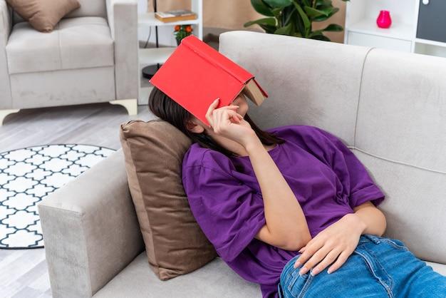 Giovane ragazza in abiti casual con sulla testa che dorme trascorrendo il fine settimana a casa sdraiata su un divano in un soggiorno luminoso