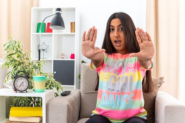 Giovane ragazza in abiti casual preoccupata di fare un gesto di arresto con le mani sedute sulla sedia in un soggiorno luminoso
