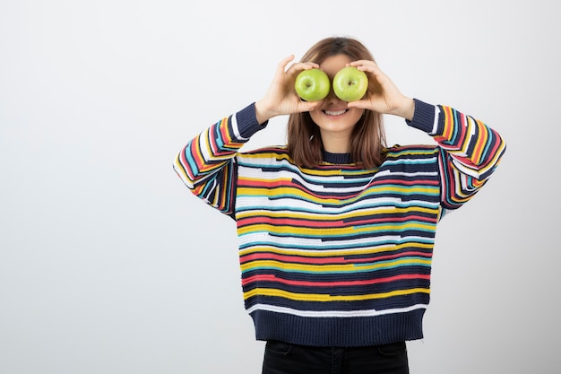 Young girl in casual outfit holding green apples in front of eyes.
