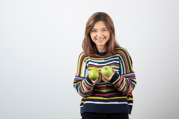 Young girl in casual outfit holding green apples with smiling expression.