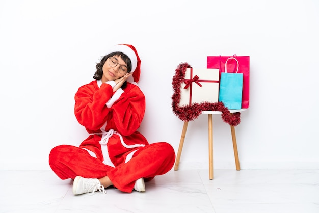 Young girl celebrating christmas sitting on the floor isolated on white bakcground making sleep gesture in dorable expression