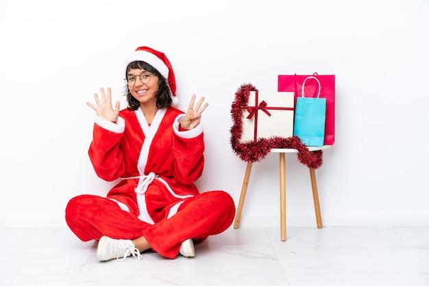 Молодая девушка празднует рождество, сидя на полу, изолированном на белом bakcground, считая восемь пальцами