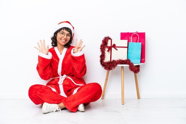 Молодая девушка празднует рождество, сидя на полу, изолированном на белом bakcground, считая девять пальцами