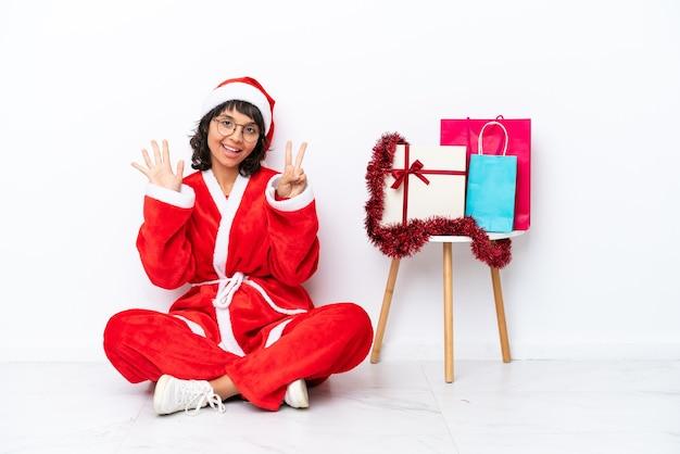 Молодая девушка празднует рождество, сидя на полу, изолированном на белом фоне, считая семь пальцами