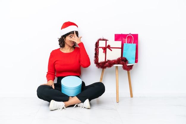 손으로 눈을 덮고 웃 고 흰색 bakcground에 고립 된 바닥에 앉아 크리스마스를 축 하 하는 어린 소녀
