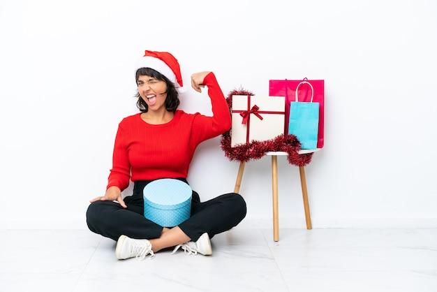 강한 제스처를 하 고 흰색 bakcground에 고립 된 바닥에 앉아 크리스마스를 축 하 하는 어린 소녀