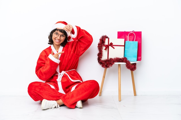 Молодая девушка празднует рождество, сидя на полу, изолированном на белом bakcground, фокусируя лицо. обрамление символа