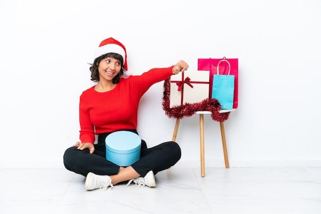 흰색 bakcground에 격리된 바닥에 앉아 크리스마스를 축하하는 어린 소녀가 엄지손가락 제스처를 제공합니다.