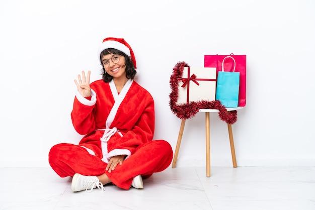 Молодая девушка празднует рождество, сидя на полу, изолированном на белом bakcground, счастлива и считает четыре пальцами