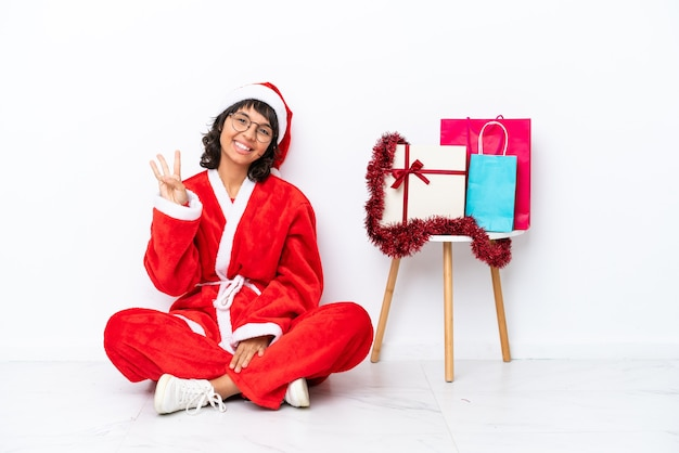 Молодая девушка празднует рождество, сидя на полу, изолированном на белом bakcground, счастлива и считает три пальцами