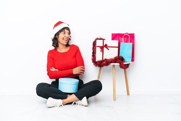 Молодая девушка празднует рождество, сидя на полу, изолированном на белом bakcground, счастлива и улыбается
