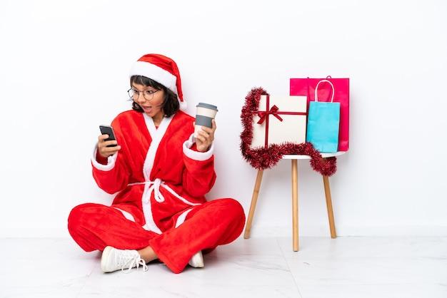 흰색 bakcground에 격리된 바닥에 앉아 크리스마스를 축하하는 어린 소녀는 테이크아웃 커피와 모바일을 들고 있습니다.