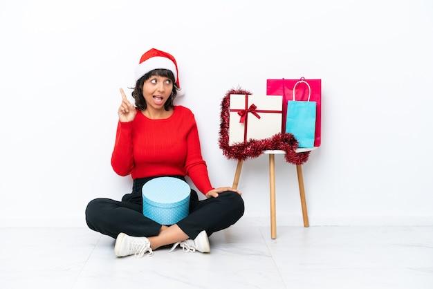 흰색 bakcground에 격리된 바닥에 앉아 크리스마스를 축하하는 어린 소녀는 손가락을 들어올리면서 솔루션을 실현하려고 합니다.