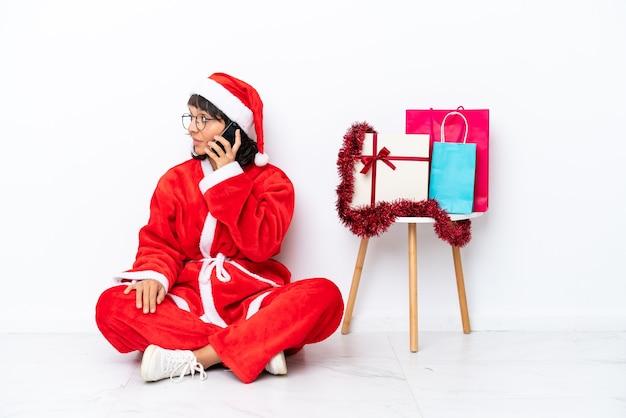 크리스마스를 축하하는 어린 소녀는 흰색 bakcground에 격리된 바닥에 앉아 누군가와 휴대전화로 대화를 나눴습니다.