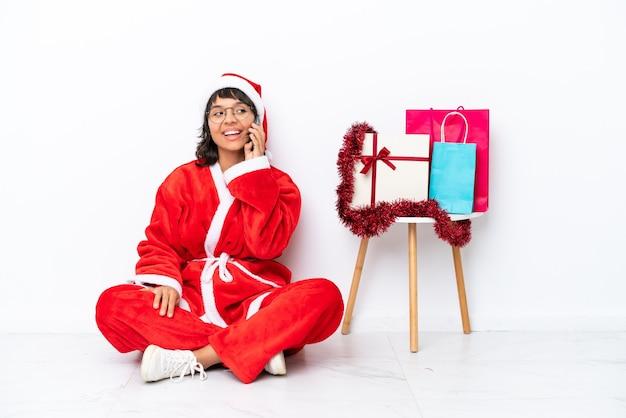 휴대 전화와 대화를 유지 하는 흰색 bakcground에 고립 된 바닥에 앉아 크리스마스를 축 하 하는 어린 소녀
