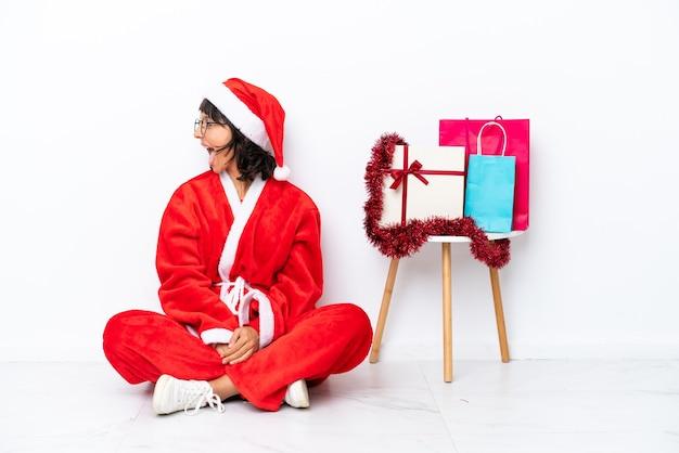 측면 위치에서 웃 고 흰색 bakcground에 고립 된 바닥에 앉아 크리스마스를 축 하 하는 어린 소녀