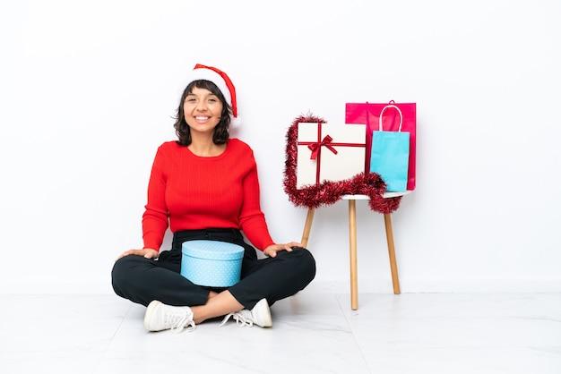 Молодая девушка празднует рождество, сидя на полу, изолированном на белом bakcground смеясь