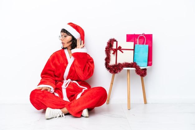 Молодая девушка празднует рождество, сидя на полу, изолированном на белом bakcground, слушая что-то, положив руку на ухо