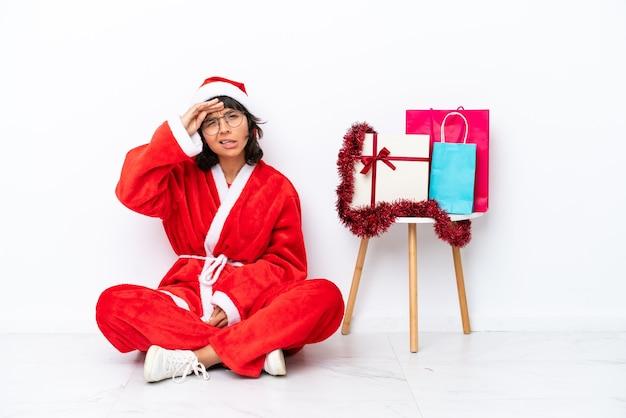 Молодая девушка празднует рождество, сидя на полу, изолированном на белом bakcground, глядя вдаль рукой, чтобы что-то посмотреть
