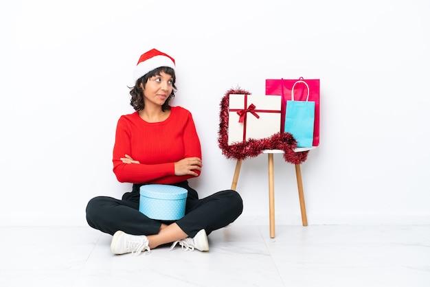 Молодая девушка празднует рождество, сидя на полу, изолированном на белом bakcground, глядя на сторону