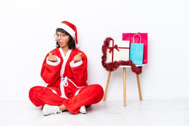 Молодая девушка празднует рождество, сидя на полу, изолированном на белом bakcground, делая денежный жест