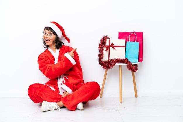 다시 가리키는 흰색 bakcground에 고립 된 바닥에 앉아 크리스마스를 축 하 하는 어린 소녀