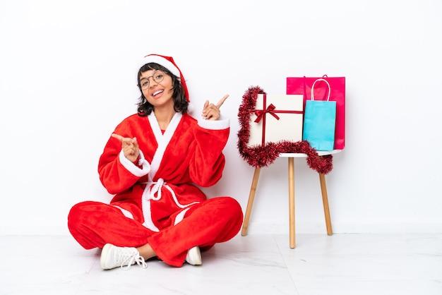 흰색 bakcground에 고립 된 바닥에 앉아 크리스마스를 축하하는 어린 소녀는 측면과 행복에 손가락을 가리키는