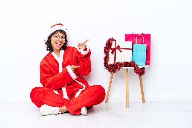 Молодая девушка празднует рождество, сидя на полу, изолированном на белом bakcground, указывая пальцем в сторону и представляя продукт