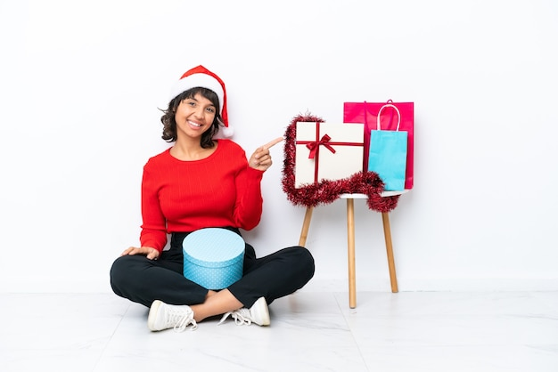 Молодая девушка празднует рождество, сидя на полу, изолированном на белом фоне, указывая пальцем в сторону