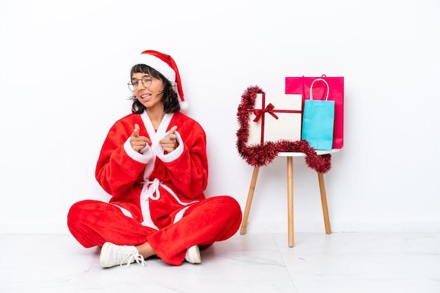 흰색 bakcground에 격리된 바닥에 앉아 앞을 가리키고 웃고 있는 크리스마스를 축하하는 어린 소녀