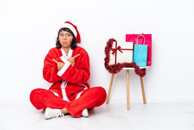 Молодая девушка празднует рождество, сидя на полу, изолированном на белом bakcground, указывая на боковые стороны, имея сомнения