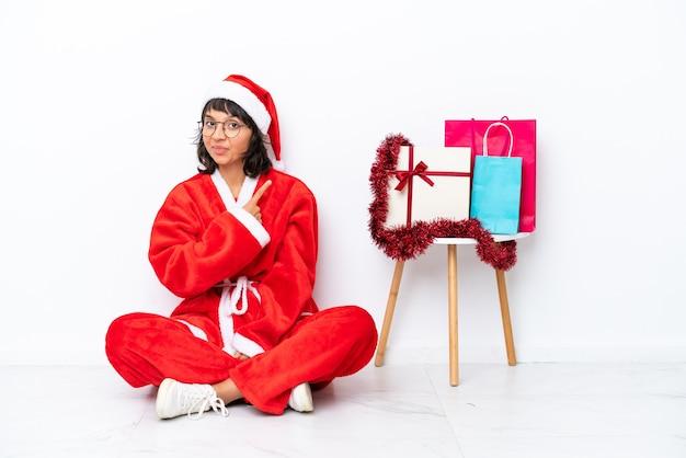 제품을 제시하기 위해 측면을 가리키는 흰색 bakcground에 격리된 바닥에 앉아 크리스마스를 축하하는 어린 소녀
