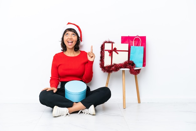 Молодая девушка празднует рождество, сидя на полу, изолированном на белом bakcground, указывая вверх и удивлен