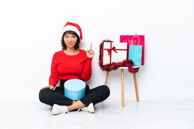 Молодая девушка празднует рождество, сидя на полу, изолированном на белом фоне, указывая указательным пальцем - отличная идея