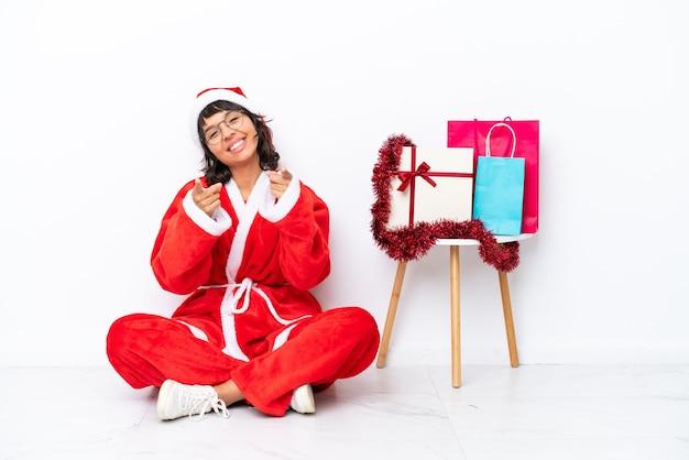 흰색 bakcground에 격리된 바닥에 앉아 크리스마스를 축하하는 어린 소녀는 웃고 있는 동안 당신을 손가락으로 가리킵니다.