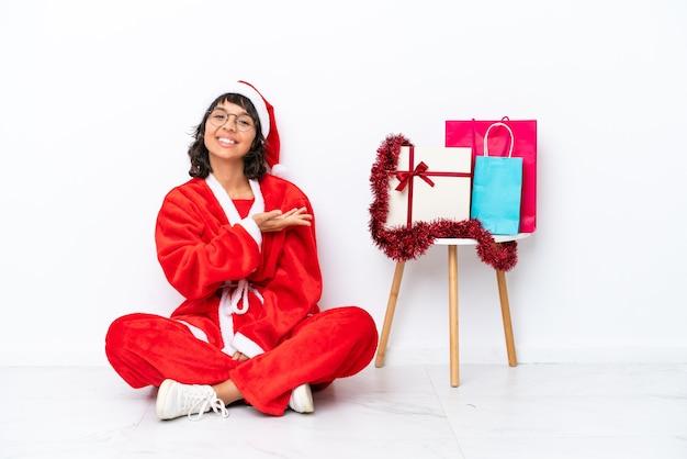 흰색 bakcground에 격리된 바닥에 앉아 크리스마스를 축하하는 어린 소녀가 웃고 있는 동안 아이디어를 제시합니다.