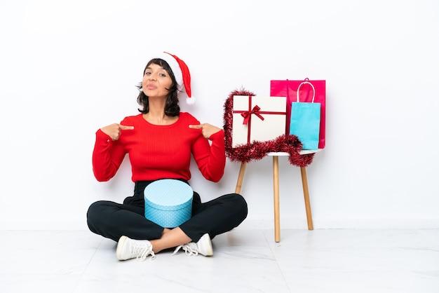 자랑스럽고 자기 만족스러운 흰색 bakcground에 격리된 바닥에 앉아 크리스마스를 축하하는 어린 소녀