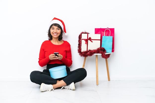 흰색 bakcground에 격리된 바닥에 앉아 크리스마스를 축하하는 어린 소녀가 모바일로 메시지를 보냅니다.