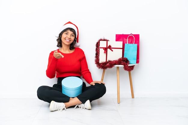 Молодая девушка празднует рождество, сидя на полу, изолированном на белом фоне, пожимая руку для заключения хорошей сделки