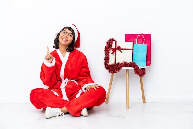 Молодая девушка празднует рождество, сидя на полу, изолированном на белом bakcground, показывает и поднимает палец в знак лучших