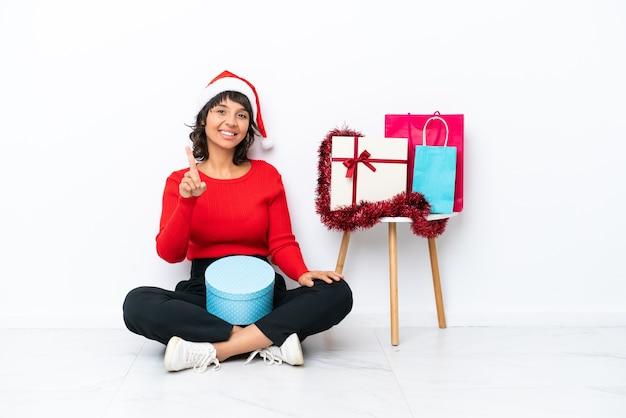 Молодая девушка празднует рождество, сидя на полу, изолированном на белом bakcground, показывая и поднимая палец