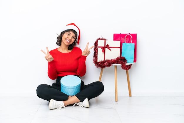 두 손으로 승리 기호를 보여주는 흰색 bakcground에 고립 된 바닥에 앉아 크리스마스를 축하하는 어린 소녀