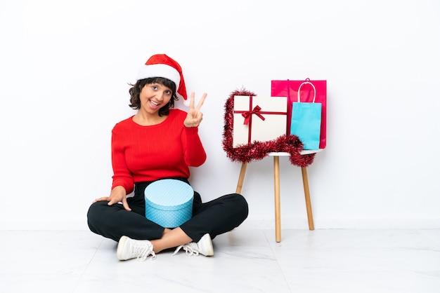 흰색 bakcground에 격리된 바닥에 앉아 크리스마스를 축하하는 어린 소녀가 웃고 승리 기호를 보여줍니다.