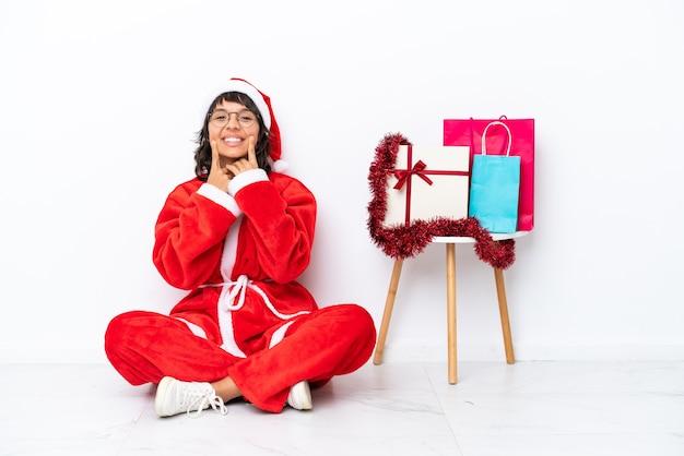 행복하고 즐거운 표정으로 웃고 있는 흰색 bakcground에 격리된 바닥에 앉아 크리스마스를 축하하는 어린 소녀