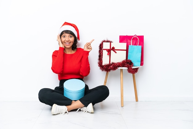 Молодая девушка празднует рождество, сидя на полу, изолированном на белом bakcground, удивлена и показывает пальцем в сторону