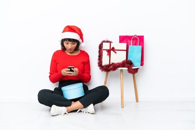 흰색 bakcground에 격리된 바닥에 앉아 크리스마스를 축하하고 메시지를 보내는 어린 소녀
